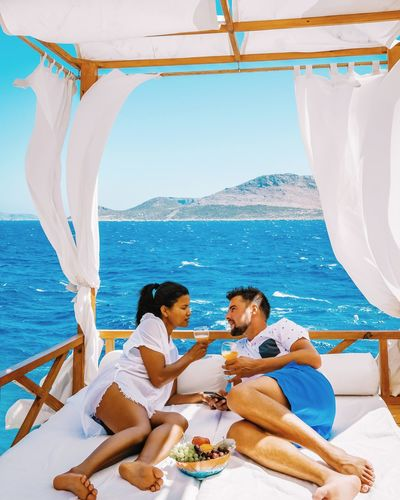 Couple Talking While Relaxing On Bed In Boat Against Clear Sky