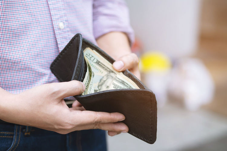 Midsection of man holding wallet with paper currency