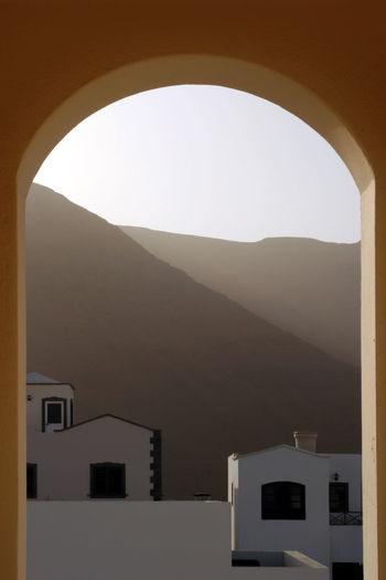 Building against clear sky seen through arch window