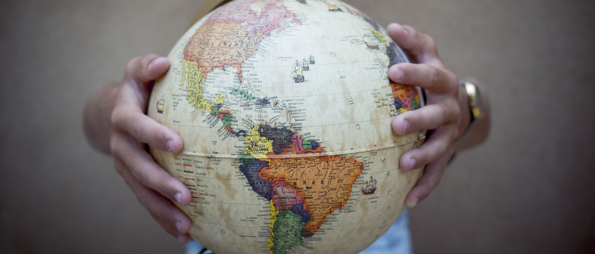 Cropped hands holding globe
