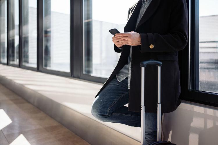 Man using mobile phone at window