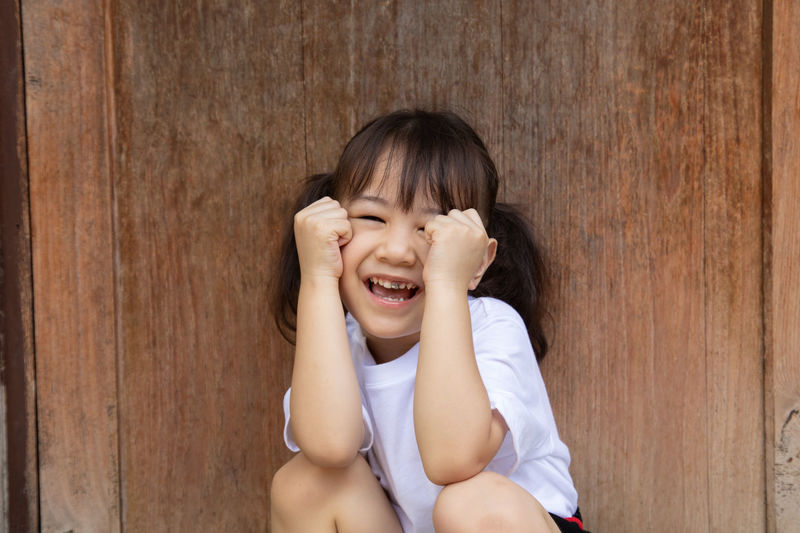 Portrait of cute girl smiling against wooden wall