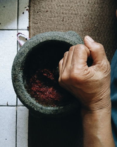 Cropped Hand Of Person Using Mortar And Pestle At Home