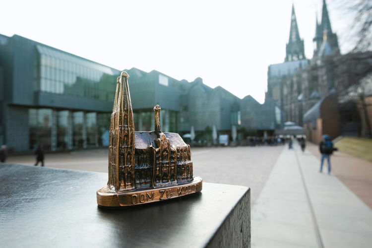Close-up of cologne cathedral model on retaining wall with museum in background