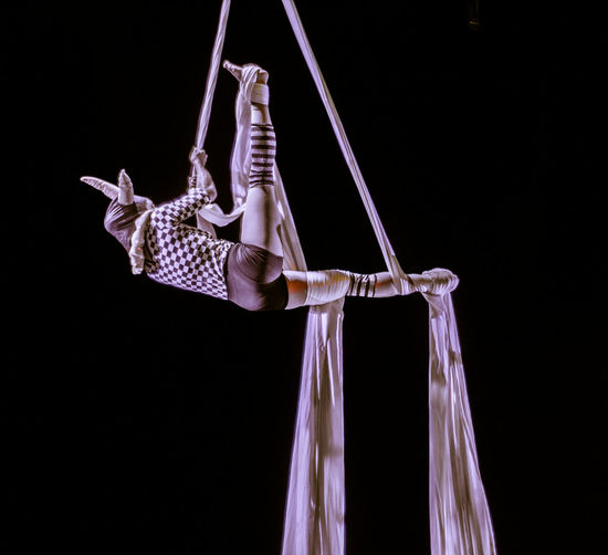 Low Angle View Of Woman Performing Over Black Background