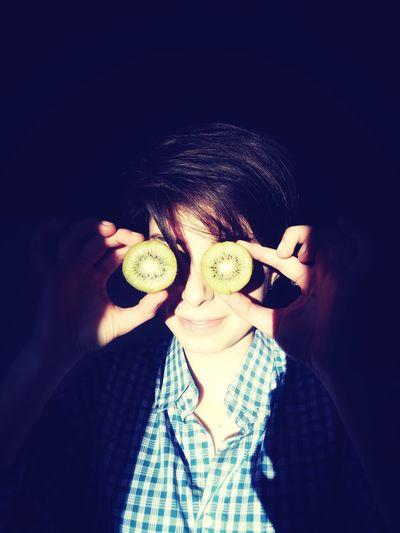 Woman holding kiwi slices on eyes against black background