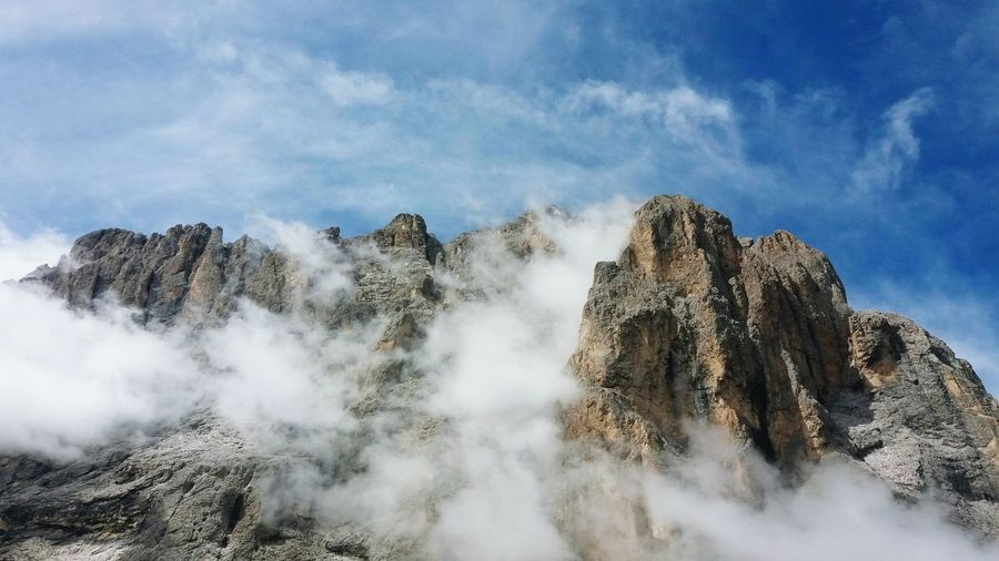 Low angle view of rocks in mountains against sky