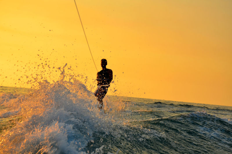 Man Kiteboarding On Sea Against Clear Sky During Sunset