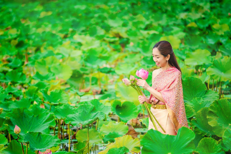 Young woman smiling while holding plants