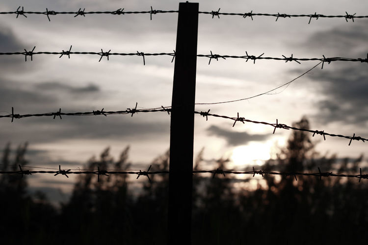 Close-up of silhouette barbed wire fence against sky