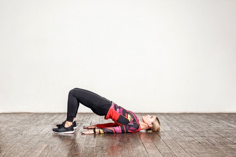 Young woman lying on floor against wall