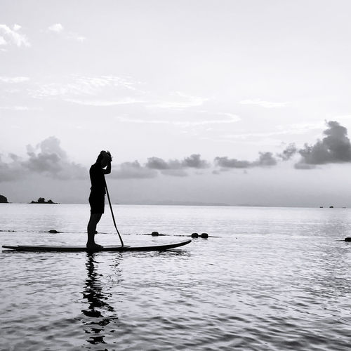 Silhouette person standing on sea against sky