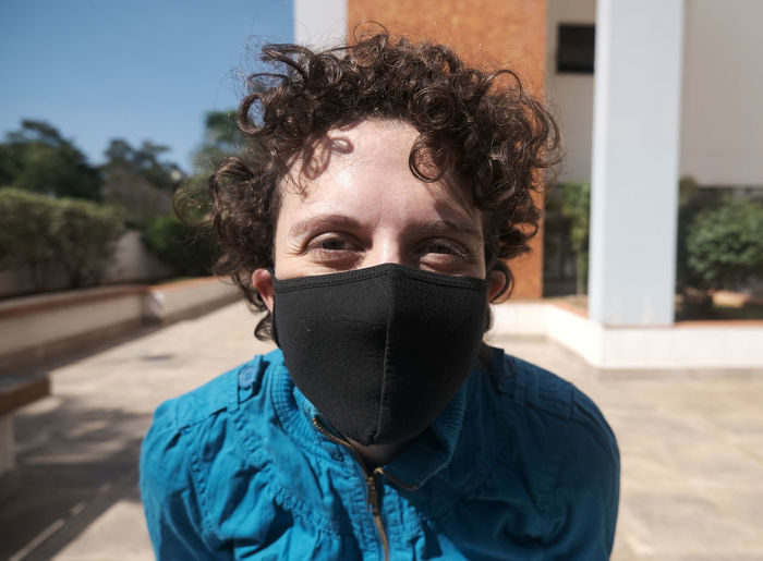 Brazilian curly hair woman using mask on a sunny day.