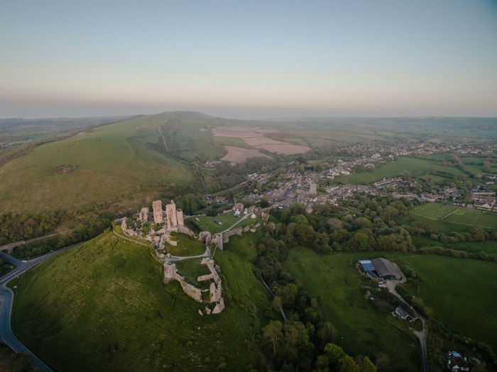 An aerial view of Corfe Castle in Dorset with the sun rising over the sea in the background. Corfe Castle Aerial View Aerial Photography Landscape Nature History British History Medieval Architecture Environment Architecture Built Structure Sky Ancient Civilization Outdoors Travel Destinations Tranquil Scene Building Exterior Horizon Over Water Beauty In Nature No People Morning Sunrise Historic Historical Building High Angle View Horizon