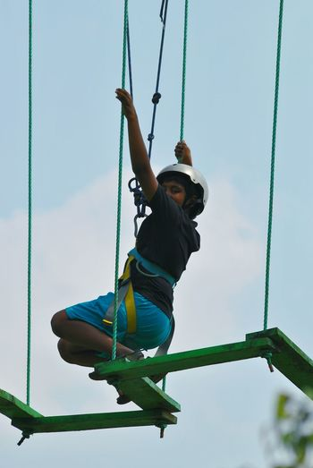 Low angle view of boy zip lining against sky