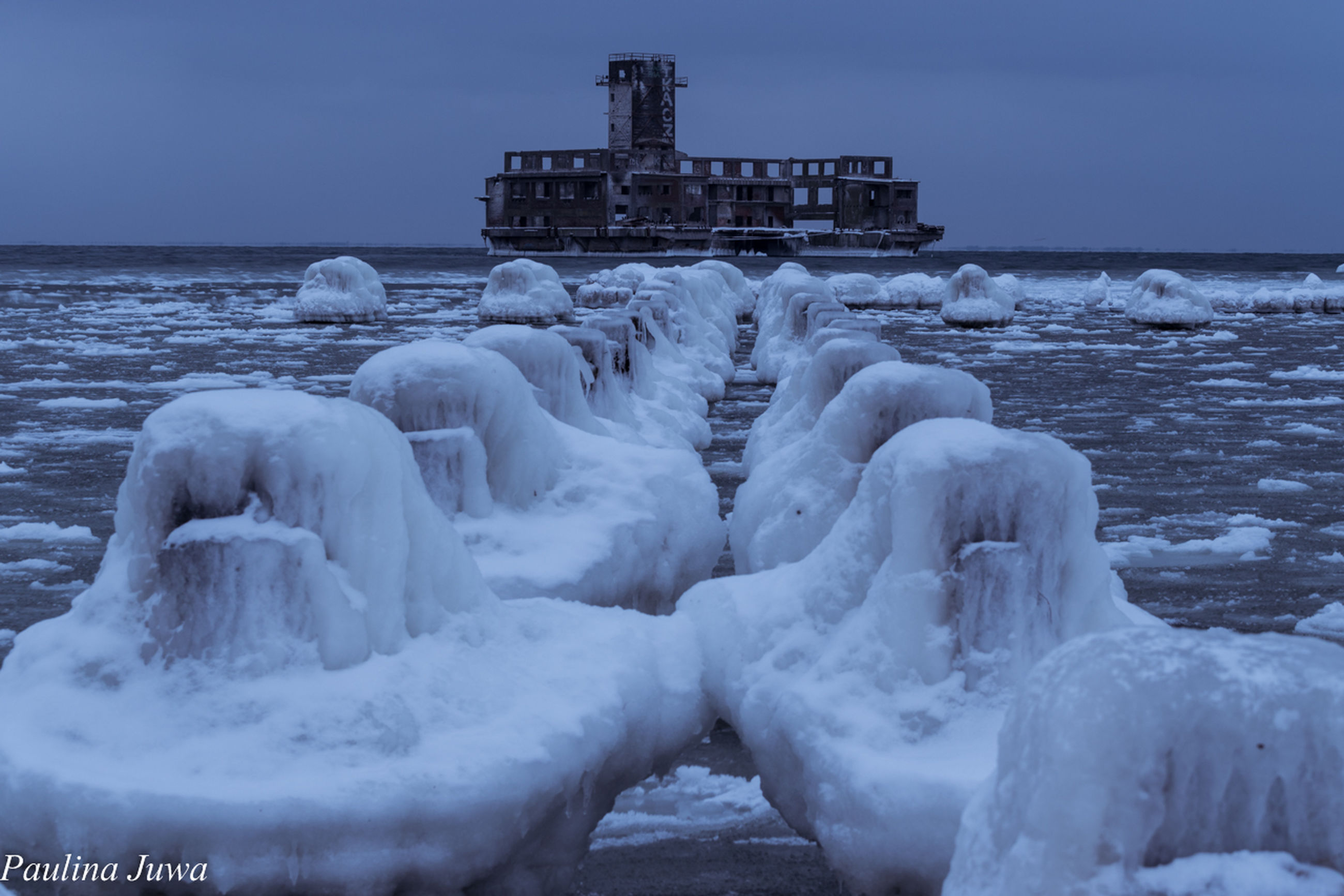 cold temperature, winter, water, sea, frozen, ice, weather, nature, snow, beauty in nature, outdoors, scenics, tranquility, sky, architecture, no people, travel destinations, built structure, day, building exterior, wave, horizon over water, iceberg