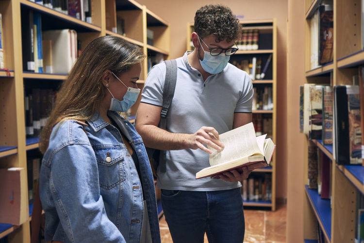 Two young people wearing masks are looking at a book in the library