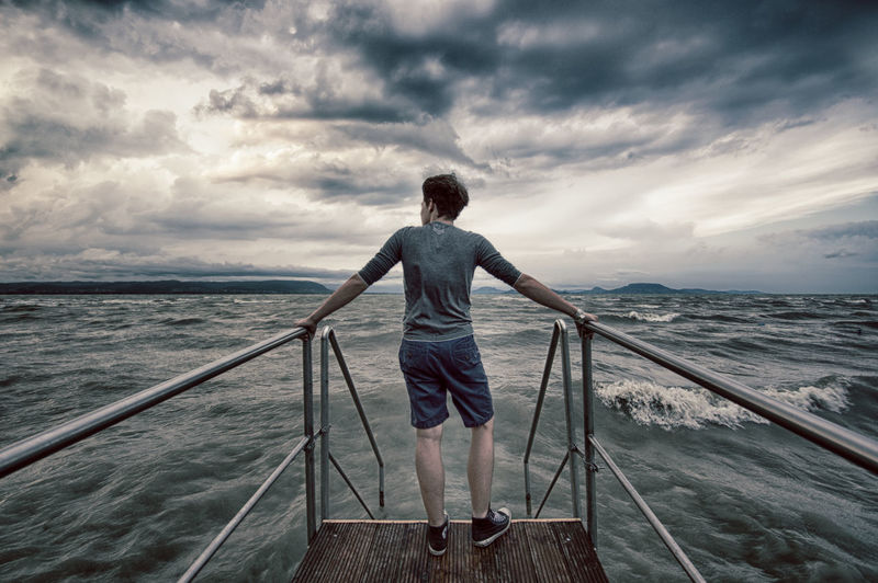 Rear View Of Man Standing On Pier In Sea Against Cloudy Sky