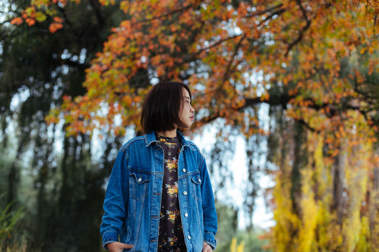 Mid adult woman looking away while standing against autumn trees