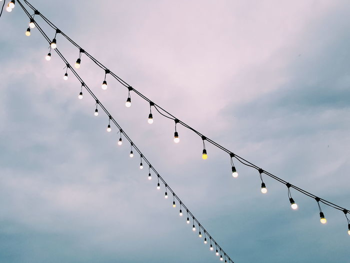 Lighting party bulbs are hang on electronic lines outdoor under cloudy sky background Bulbs Lights Backgrounds Blue Cloudy Lines Hanging Wire Outdoor Party Arrangement White Yellow Copyspace Togetherness Sky