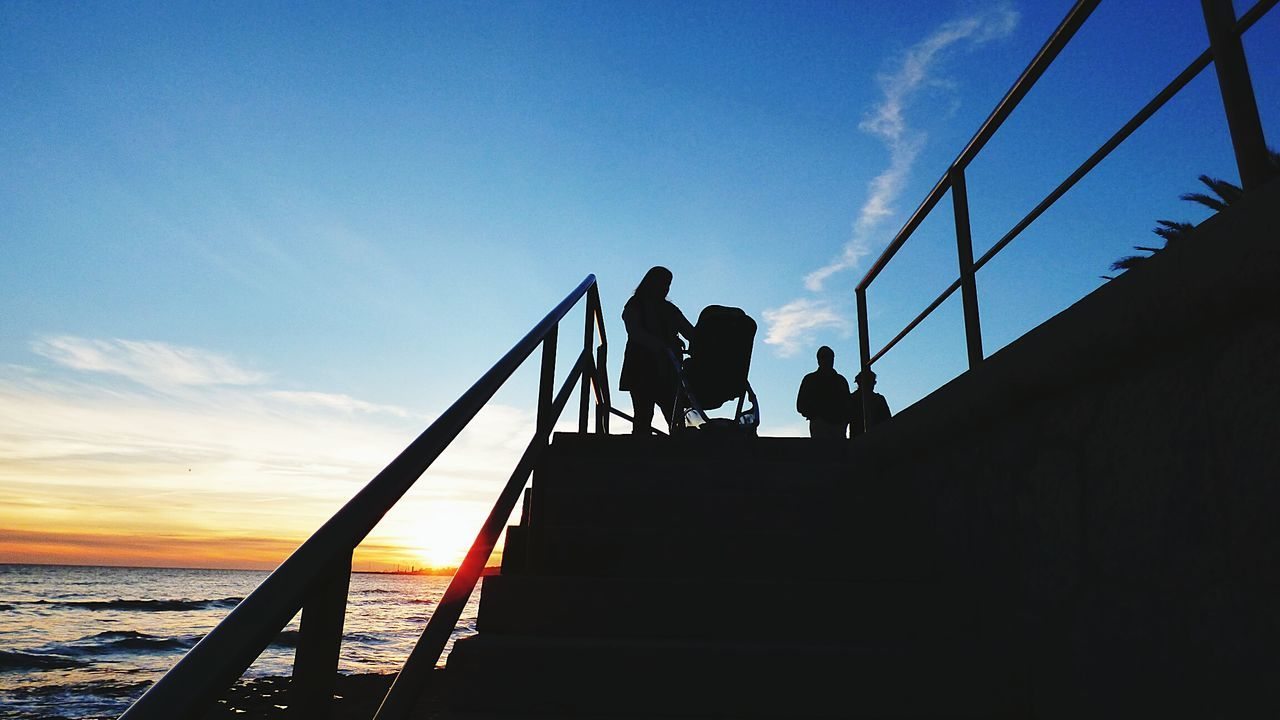 Low angle view of silhouette people standing on railing by sea