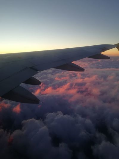 Airplane wing against sky during sunset