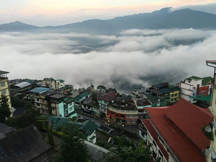 High angle view of town in foggy weather during sunset