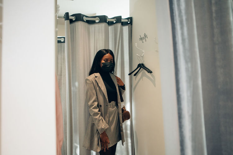 Young black woman looking to herself in the mirror of a dressing room in a fashion boutique.