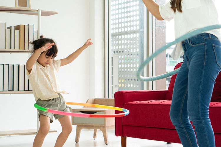 Midsection of mother and daughter playing with plastic hoops at home
