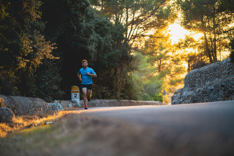 Man running on rock by trees