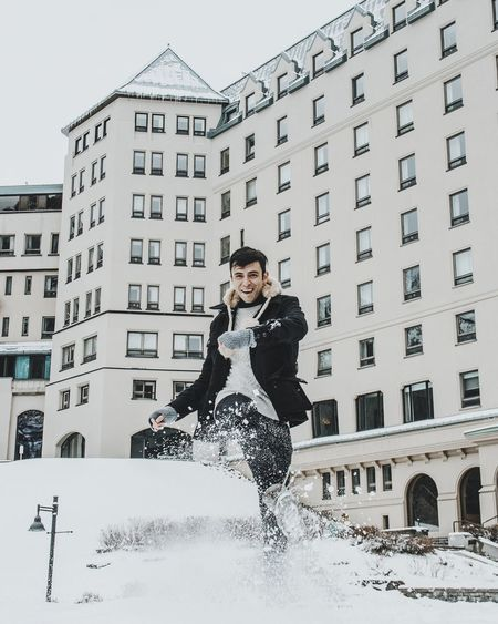 Portrait Of Smiling Man Kicking Snow