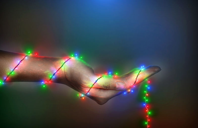 Digital composite image of hand with illuminated lights