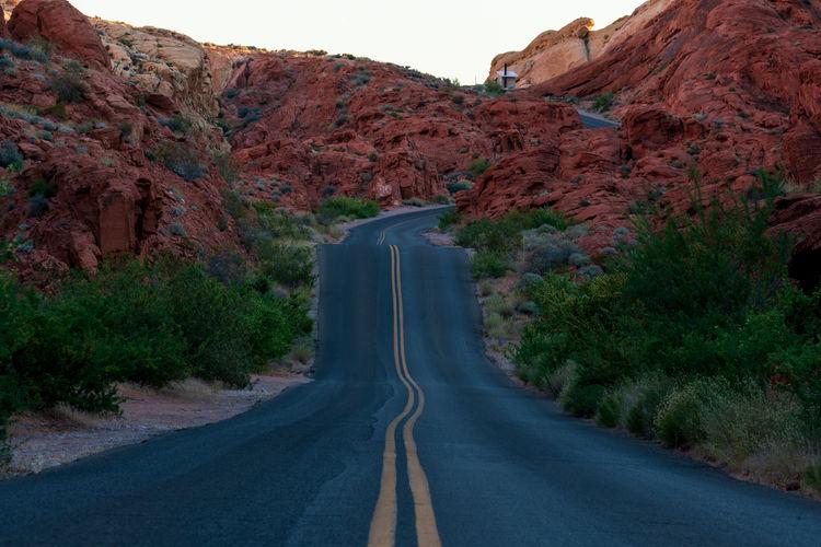 Road amidst rocks against sky