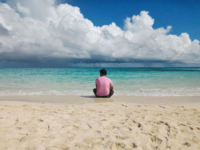 Rear view of mid adult man sitting at beach against cloudy sky during sunny day