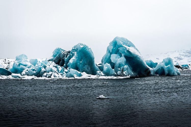 Ice floating on sea against sky