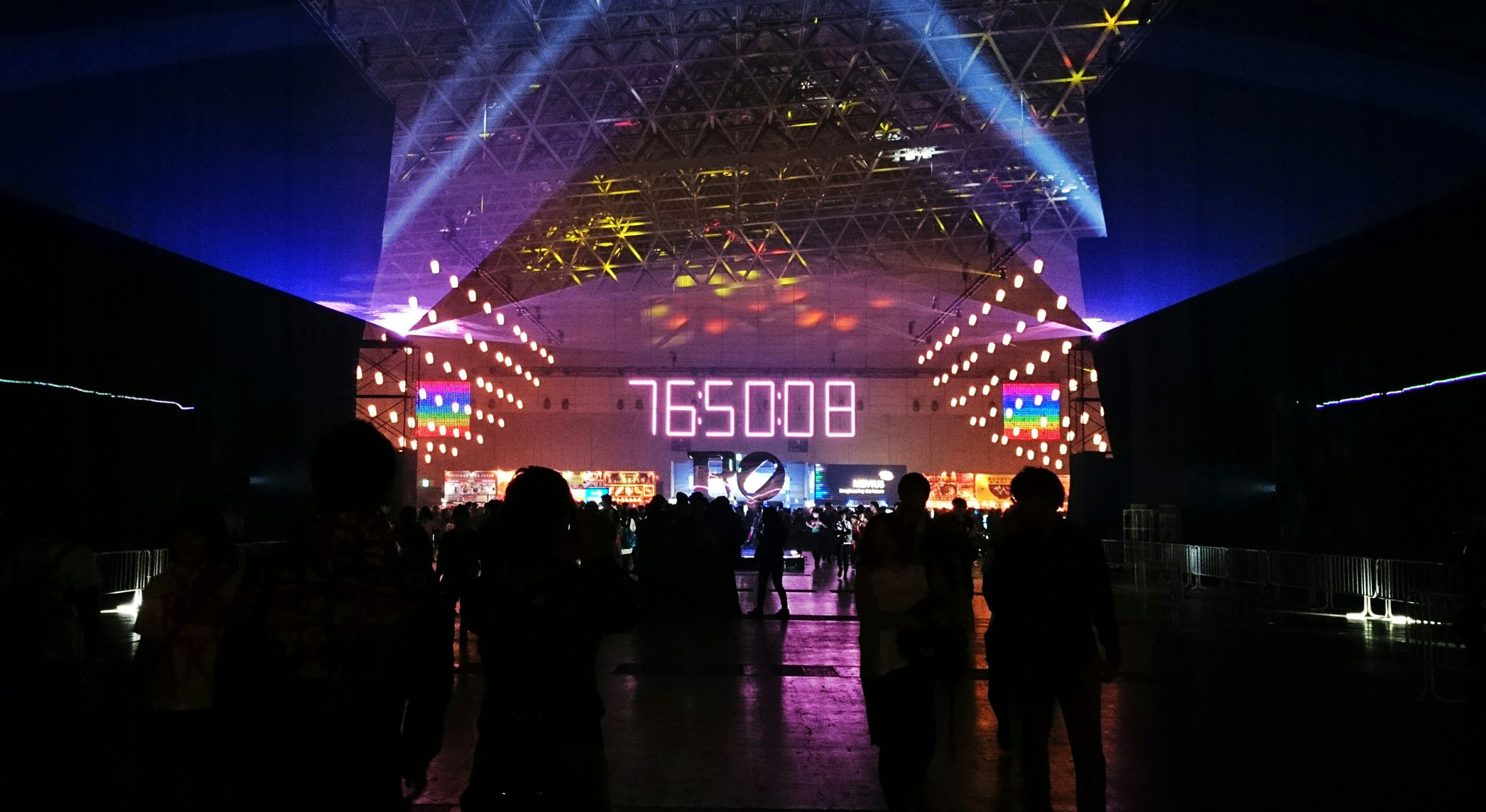 illuminated, night, large group of people, men, indoors, lifestyles, person, lighting equipment, built structure, leisure activity, architecture, text, crowd, city life, nightlife, arts culture and entertainment, light - natural phenomenon, city, communication