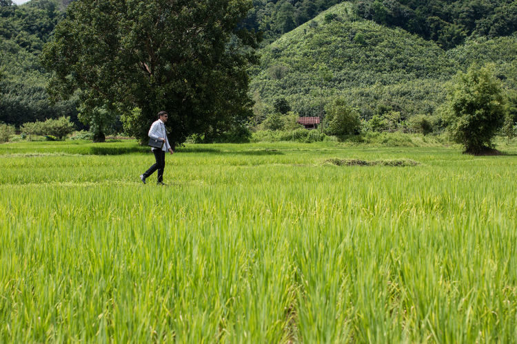 Side View Of Doctor Walking On Grassy Field Against Mountain
