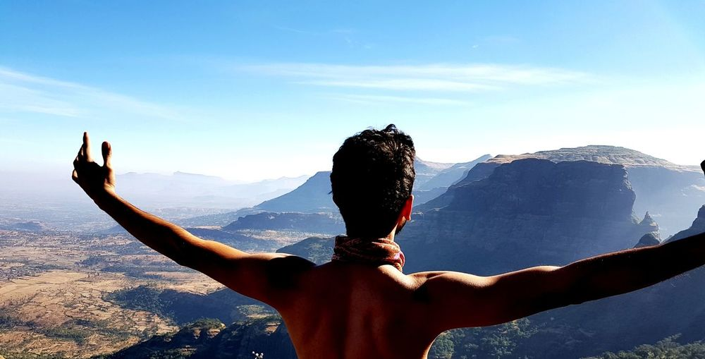 Rear view of shirtless man with arms outstretched against sky