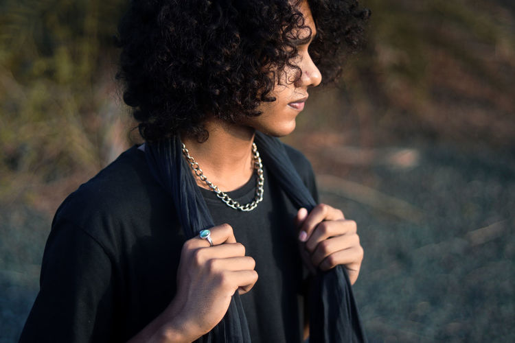 A guy with curly hair in black dress