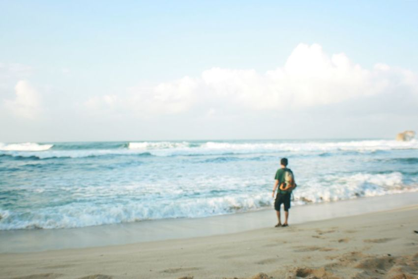 young man standing at sadranan beach Contemplation Adventure Beach Beauty In Nature Day Defocused Full Length Horizon Over Water Leisure Activity Men Nature One Person Outdoors People Real People Sand Scenics Sea Shore Sky Standing Vacations Walking Water Wave An Eye For Travel