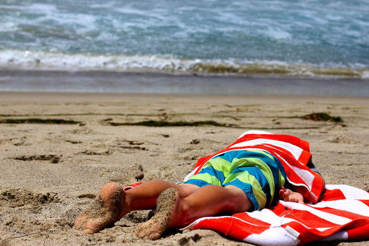 Man With Towel Lying On Front At Beach
