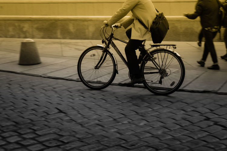 Low section of man riding bicycle on street