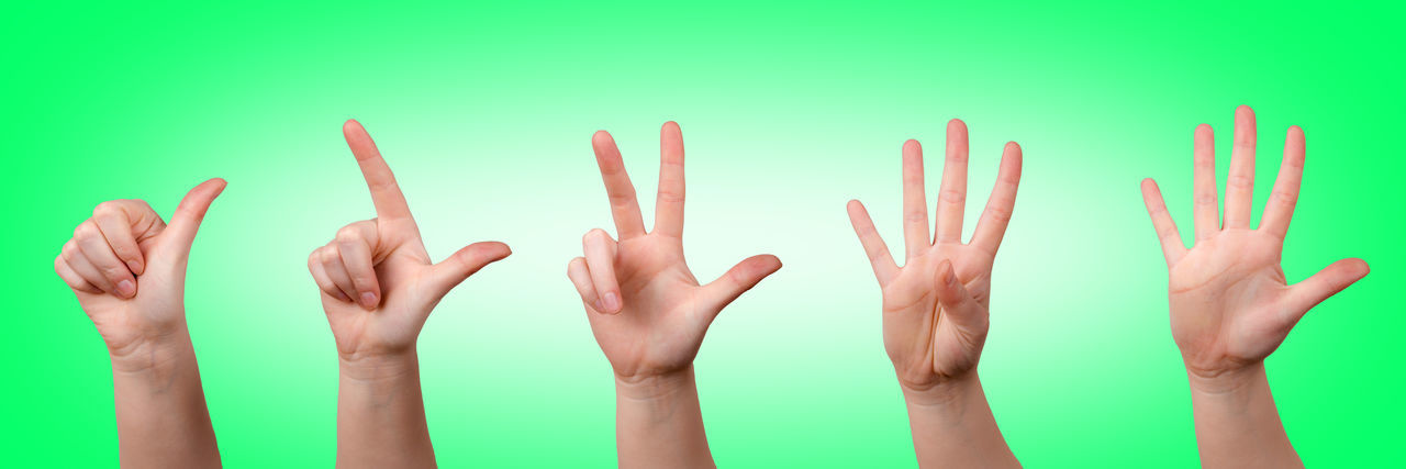 Cropped hands gesturing against green background