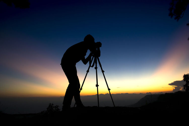 Silhouette young man photographing while standing on mountain against sky during sunset