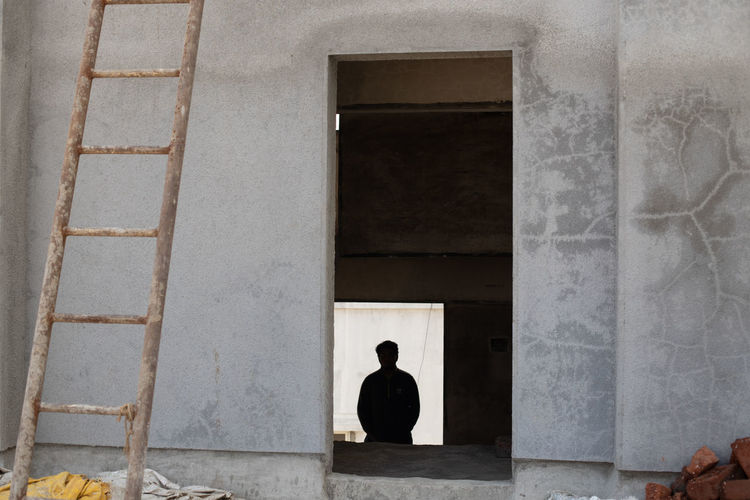 Rear view of man sitting against building
