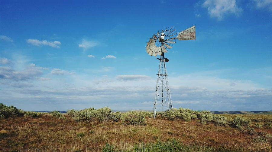 Low angle view of american-style windmill on field against cloudy blue sky