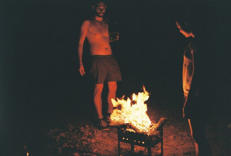 Friends standing by burning fire pit at night