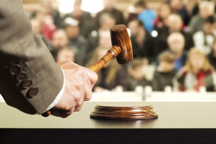 Close-up of judge hammering on gavel in court