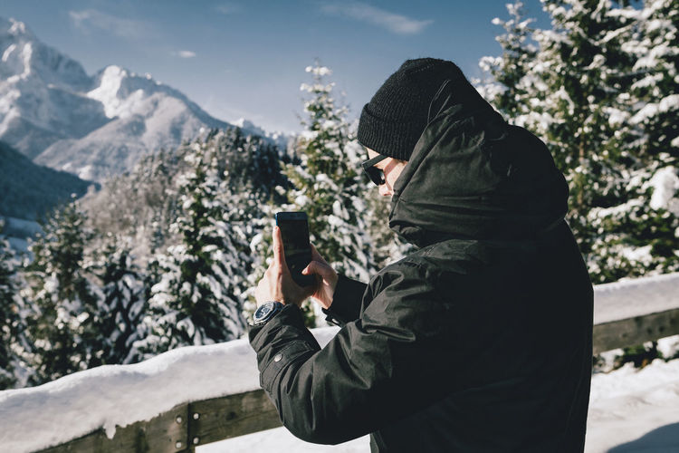 Side View Of Man Photographing With Smart Phone During Winter