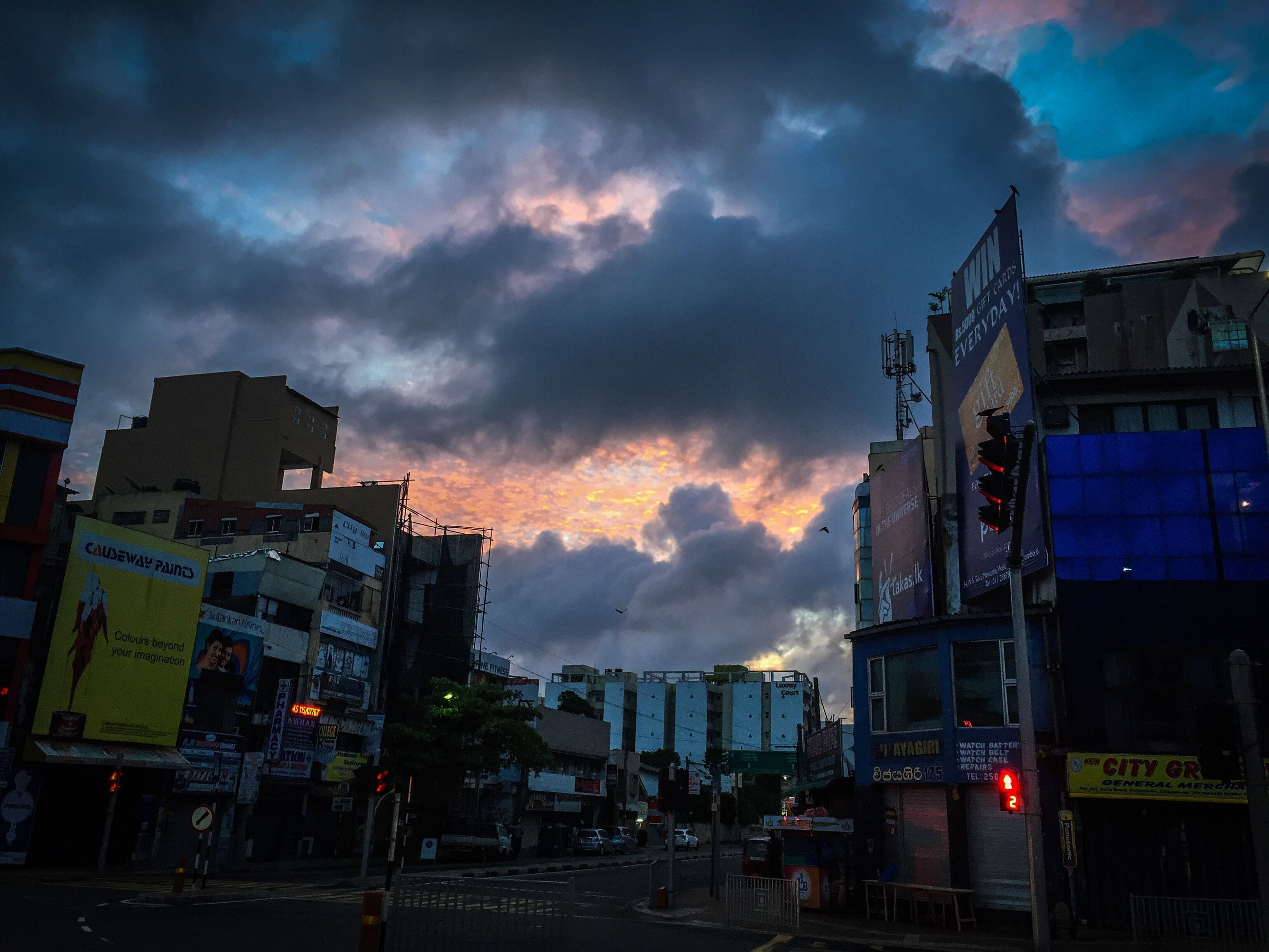architecture, building exterior, built structure, city, sky, dusk, cloud, cloud - sky, illuminated, outdoors, tall - high, city life, cloudy, moody sky, tall, no people, building story